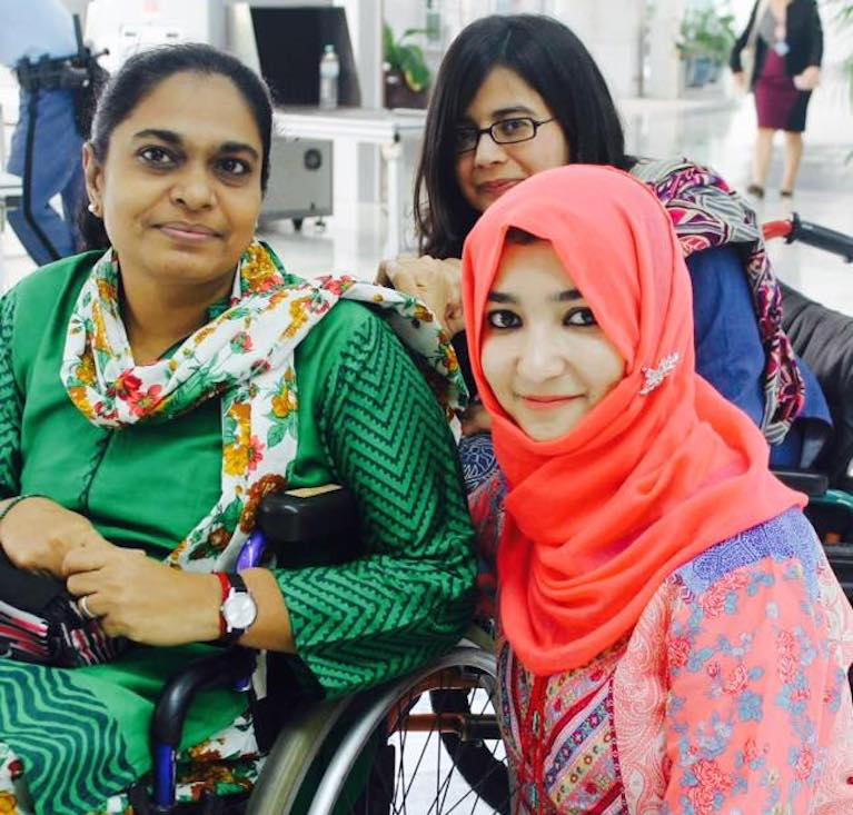 Sumaira is pictured with two woman, one in a wheelchair