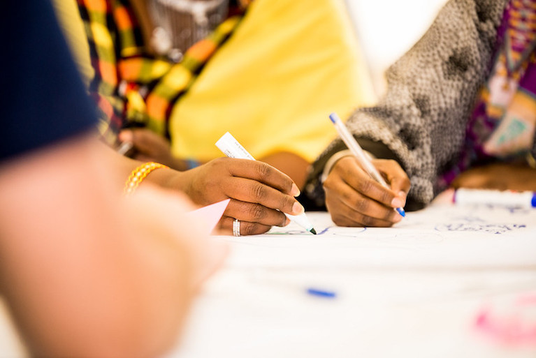 A photo of two people's hands holding pens and writing on a piece of paper