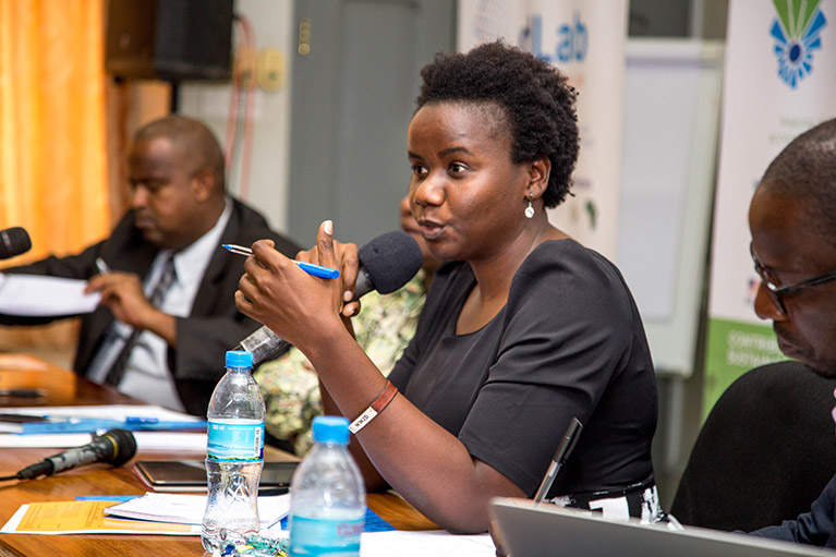 A woman speaking into a microphone at a meeting in Tanzania while two men take notes