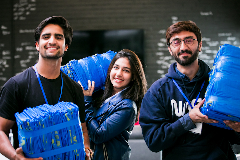 Three participants holding supplies while volunteering.