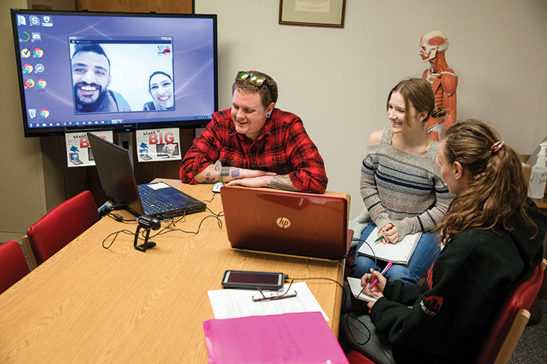 Three college students in the U.S. talking with three students from Jordan over video chat