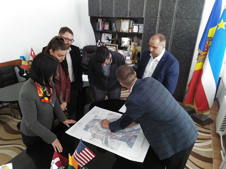 Photo of a vice-mayor in Comrat. He's leaning over a map and explaining to a small group how he uses geospatial information.