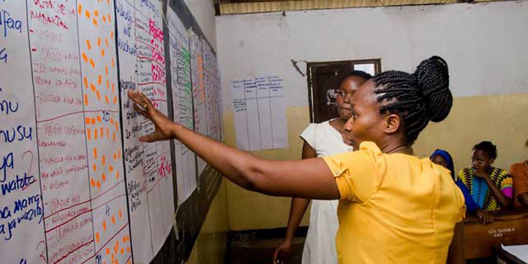 Two participants look at handwritten data and insights on large notepad pages in a classroom.
