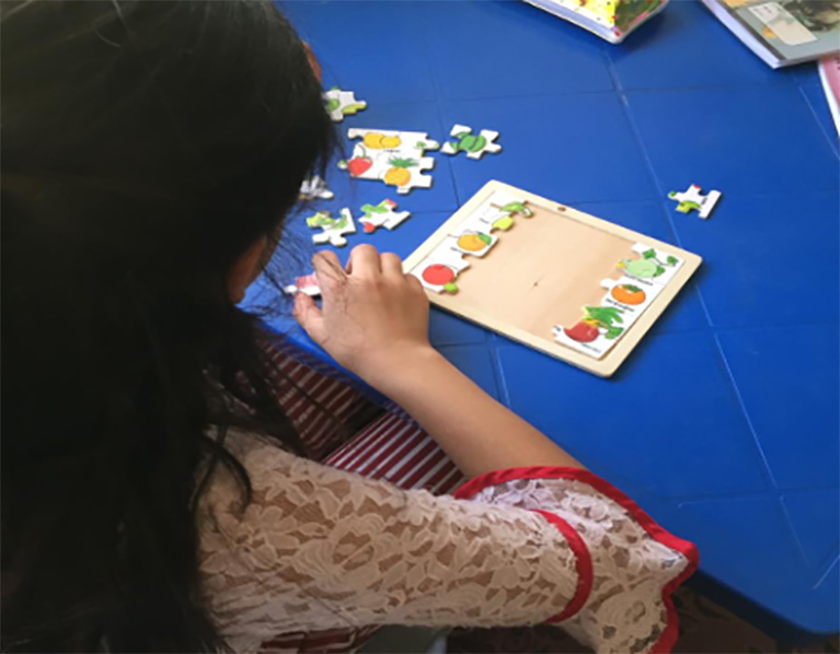 A child working on a puzzle at a table.