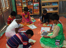 Seven children reading books and tablets on the floor in a library