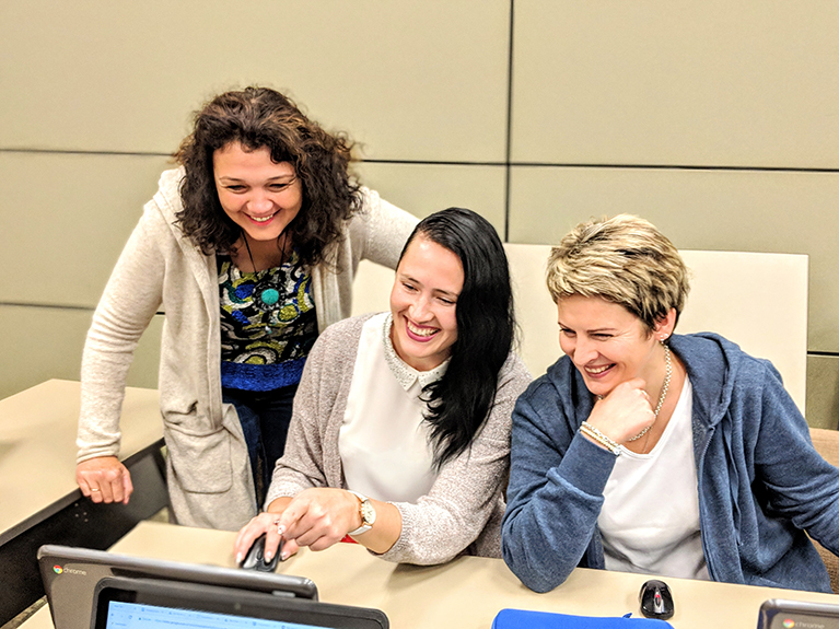 Photo of three teachers smiling and looking at a laptop.