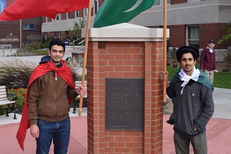 Photo of two participants who are standing outside a university.