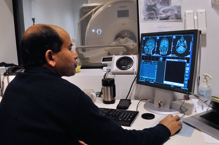 Photo of a researcher looking at brain scans on a computer in front of an MRI machine.