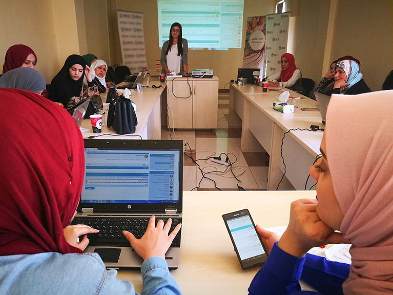 Jordanian students and a facilitator using online collaboration tools in a classroom
