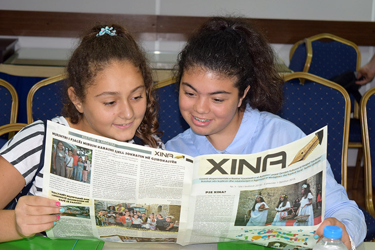 Two journalism students reading their story in the Xina newspaper