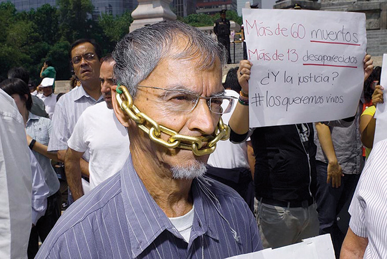 Journalists protest against rising violence during a march in Mexico. One journalist is wearing a chain, which is tied around his head and covering his mouth.