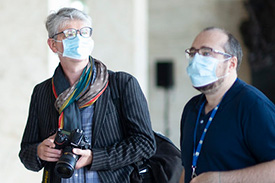 Two journalists wearing masks.