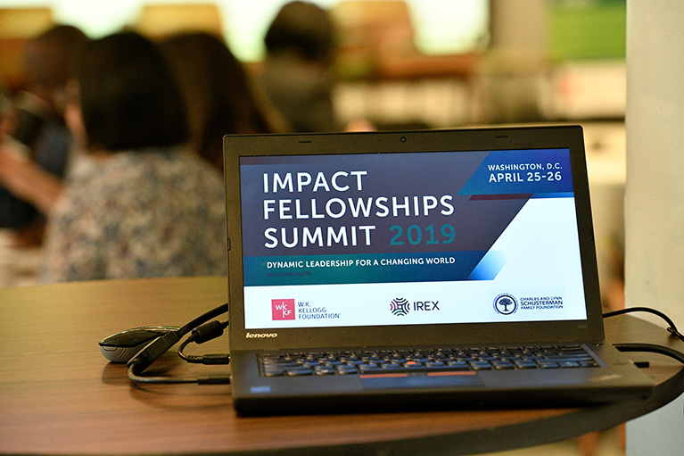 Photo of a laptop on a table at a conference. The laptop's screen says Impact Fellowships Summit 2019.