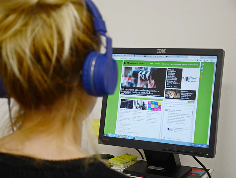 Photo of a person who is wearing headphones and looking at a news site on a desktop monitor.