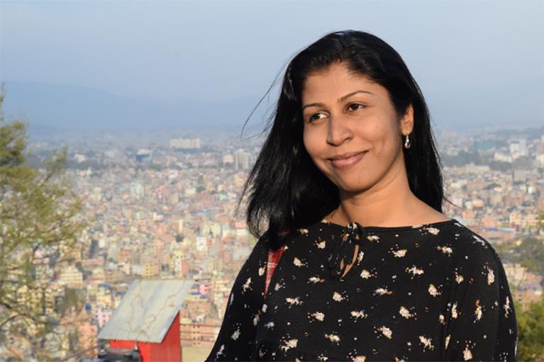 Nirasha Piyawadani on a hilltop overlooking a city.