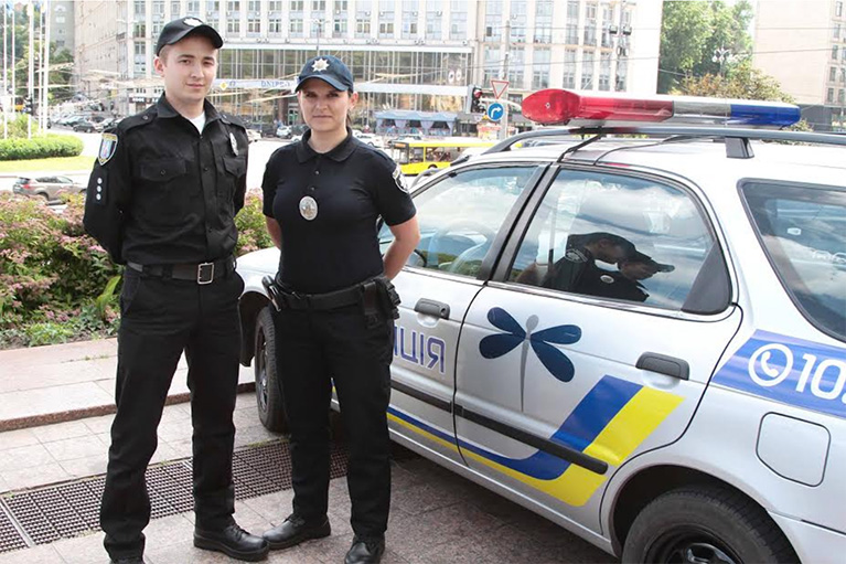 Two Ukrainian police officers standing next to a police car