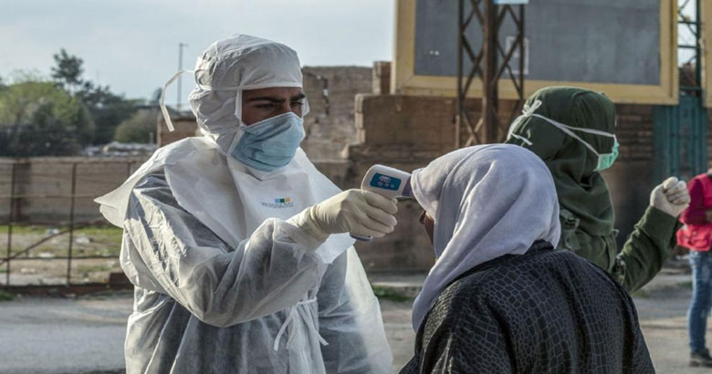 Photo of two health workers and a patient who are standing outside. One of the health workers is taking the patient's temperature.