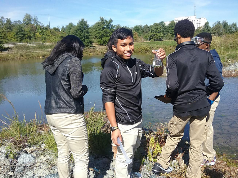 Students collecting lab samples from a river