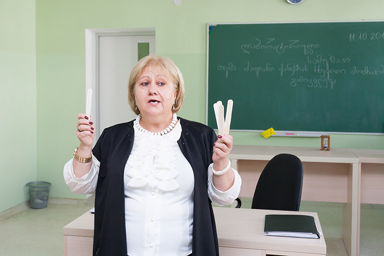 A teacher explaining a group activity in a classroom. She is holding tongue depressors in each hand.