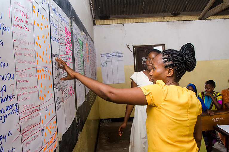Two people discussing notepad pages that are taped to a chalkboard in Tanzania. The papers are full of handwritten notes and sticky notes about citizens' priorities.