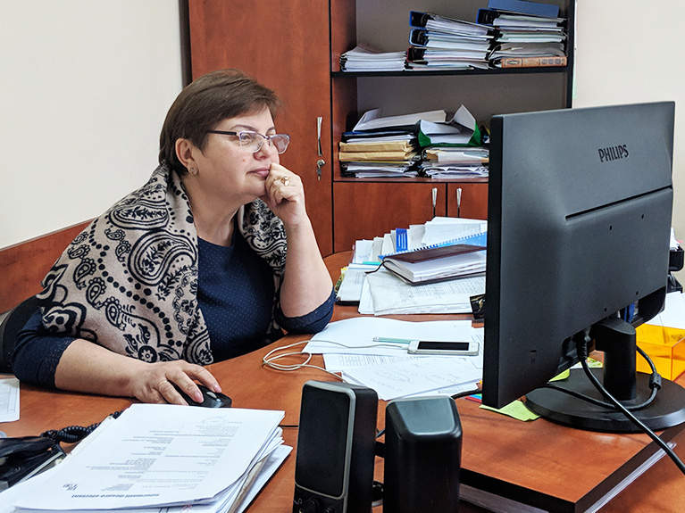 Photo of a government employee in her office in Moldova. She's testing the data tool on her computer.