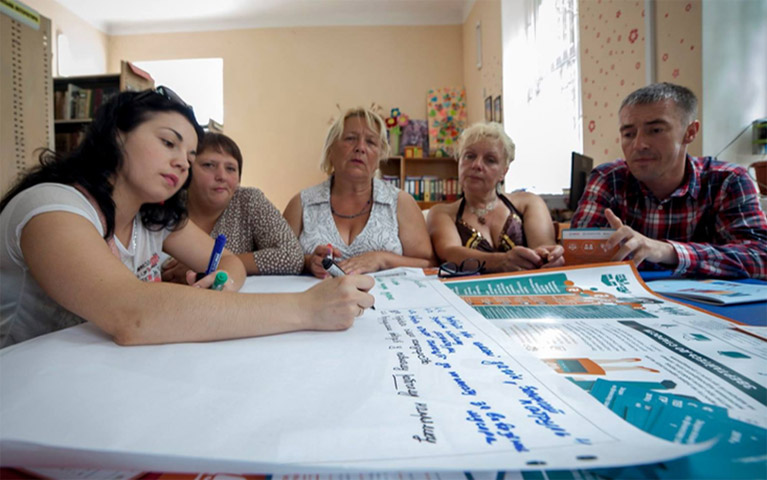 A group of Ukrainian citizens brainstorming ideas on a notepad at a table