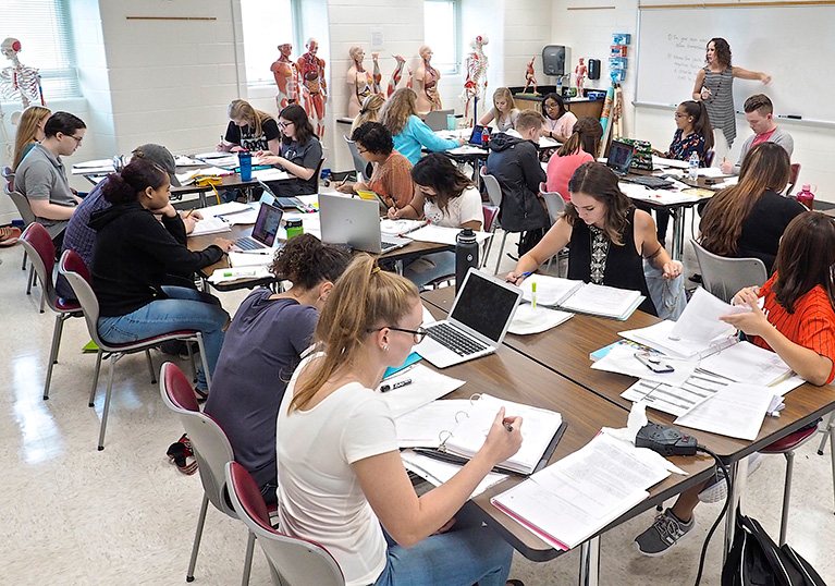 Photo of a teacher and students in a classroom. The teacher is at a whiteboard and the students are working at desks.