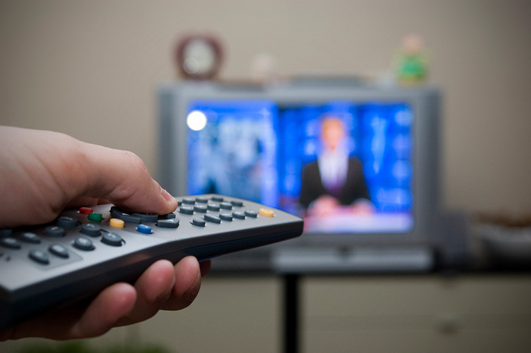 A person's hand holding a remote control in front of a TV