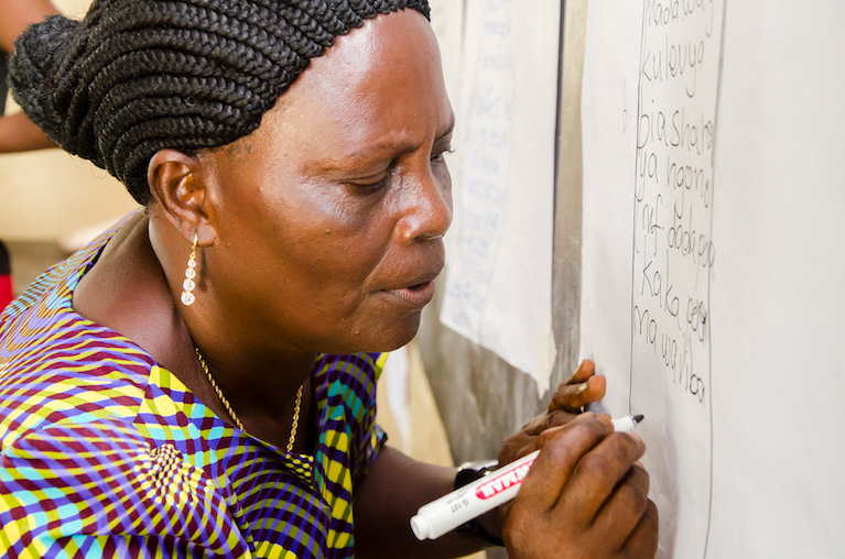 Photo of a woman writing on a page of notepad paper at a chalkboard.