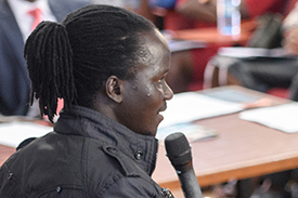 Photo of a young person speaking to an audience in an auditorium during a youth-led labor market assessment.