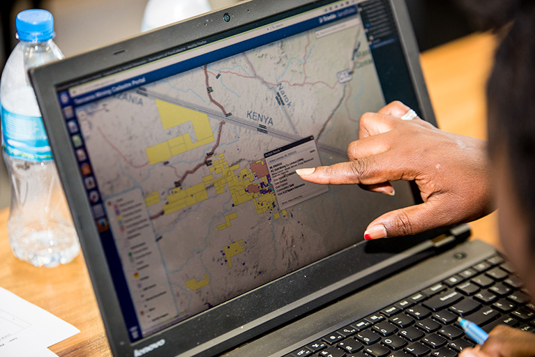 A person pointing to a laptop screen that shows data atop a map. The map focuses on a border between Tanzania and Kenya.