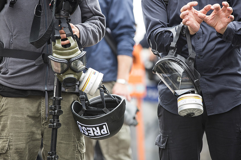 Two journalists with gas masks and helmets.
