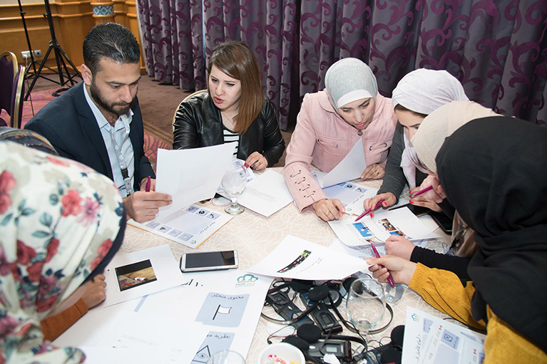Photo of seven participants at a table in Jordan. They're looking at printouts and talking to each other.