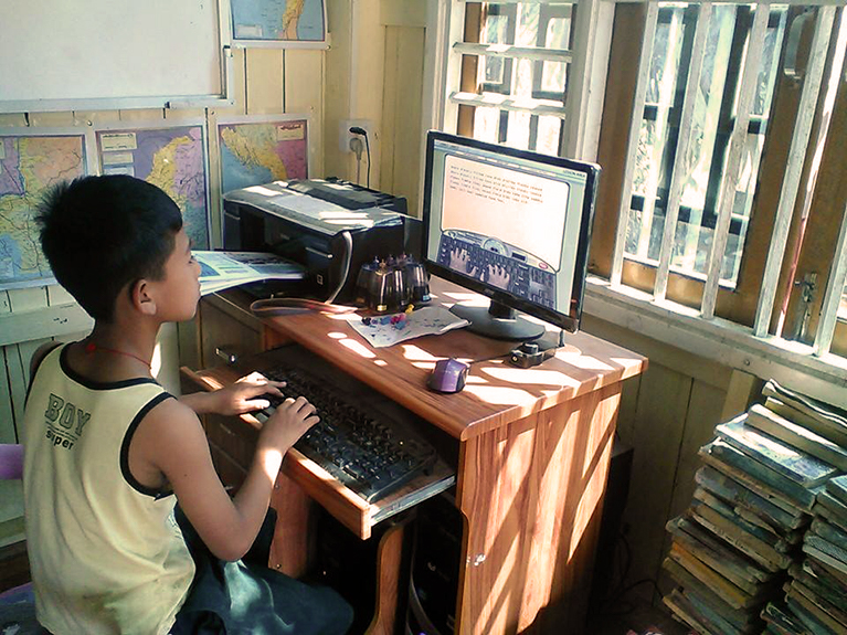A boy in Myanmar using a computer
