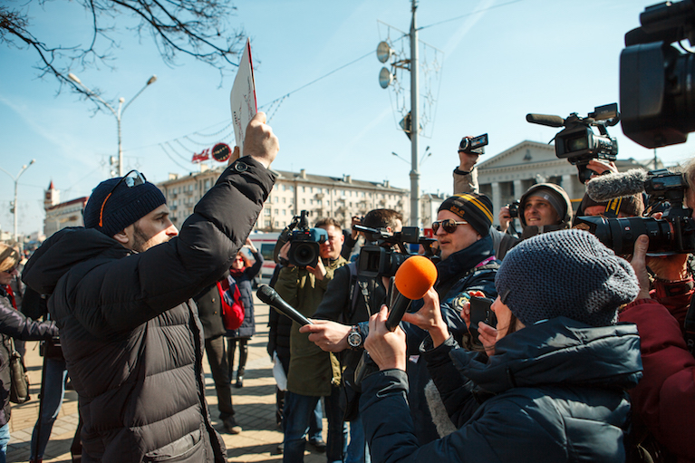A man holds a sign as journalists hold microphones and cameras