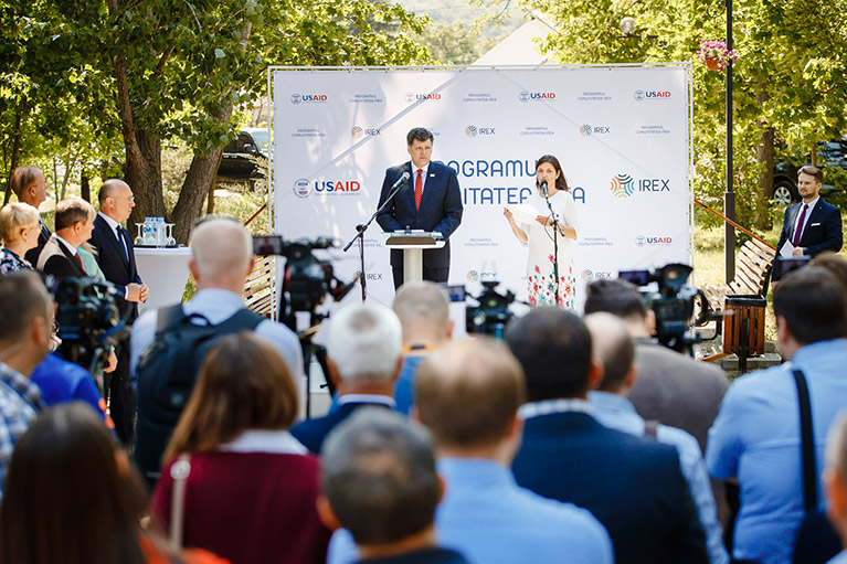 Two speakers on an outdoor stage address a standing audience at Comunitatea Mea's launch event