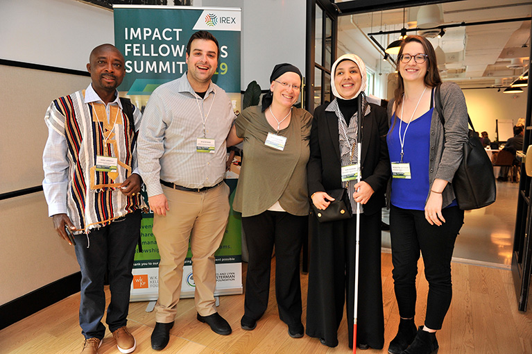 Photo of five participants from the 2019 Impact Fellowships Summit. They're standing in front of the conference's banner and smiling for the camera.