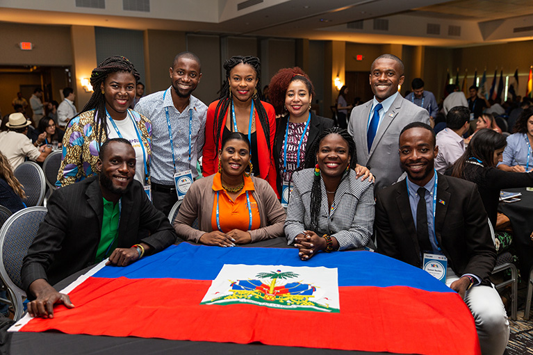 Photo of nine participants at a table in a conference hall. Haiti's flag is on the table.