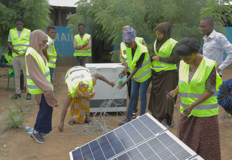 A group of young people setting up a solar panel
