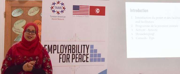 A young woman stands in front of a banner that reads Employability for Peace