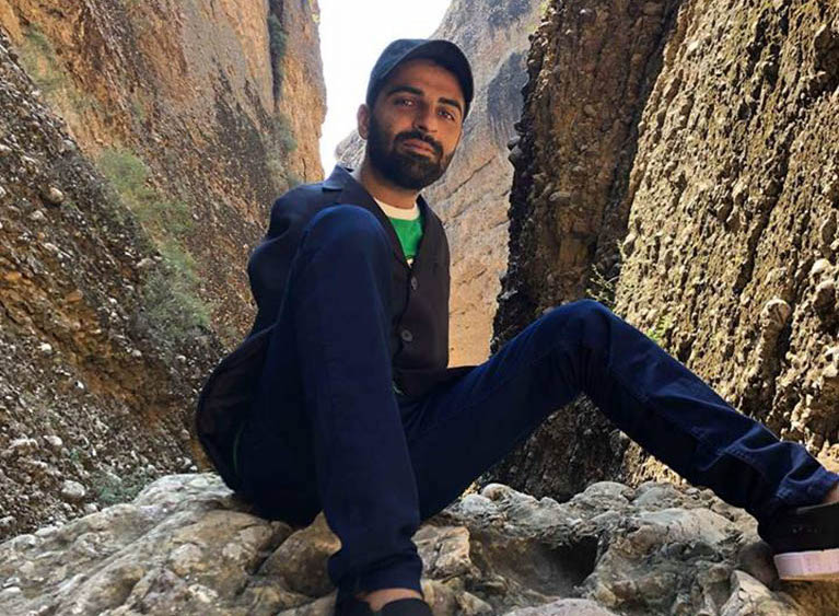 Photo of Abdul, who is sitting in a canyon.