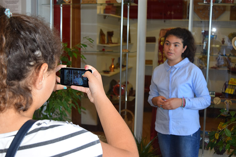 A journalism student recording another student with a smartphone