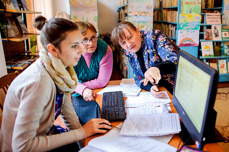 Photo of two library patrons and a librarian in front of a computer. The librarian is pointing at one side of the screen.