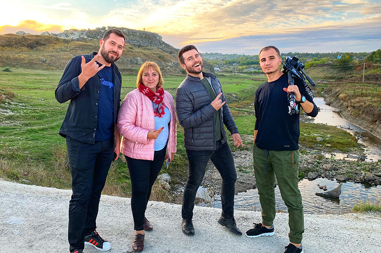 Photo of four people from the cast and crew of Tur-Retur. They're standing on a road in front of a hill and stream in Moldova.