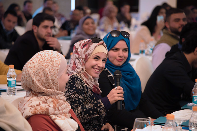Three young women at an event in Jordan. One of the women is holding a microphone.