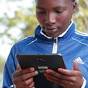 A person using a tablet while standing outside in Tanzania.