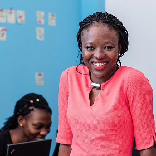 Regina Agyare, a Ghanaian software developer and Mandela Washington Fellow. She is smiling in front of a group of girls who are using laptops.