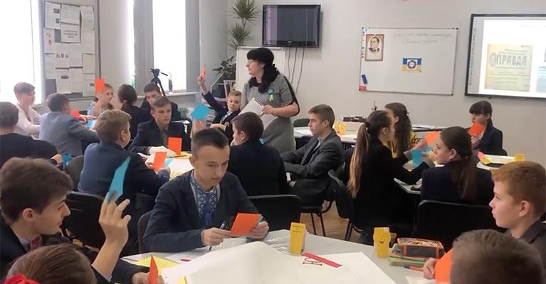 A teacher and students in a classroom in Ukraine. The students are doing a media literacy exercise with orange and blue pieces of paper.