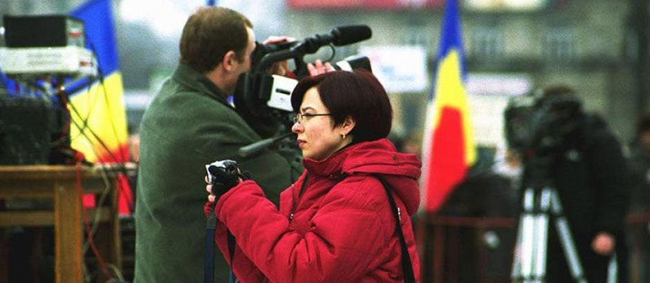 A woman with a camera and a man with a video camera outside in winter