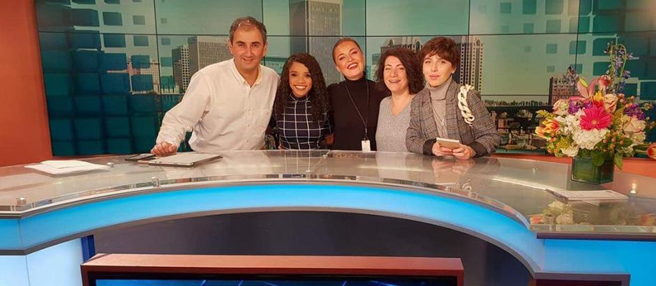 Five participants in a newsroom studio. They are standing behind a news desk and smiling.
